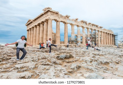 Athens, Greece - June 12, 2013: Tourist in multiple exposure posing in various poses in front of the famous Parthenon on Acropolis hill. the temple is under reconstruction surrounded by scaffolding