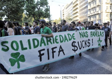 """ATHENS, GREECE - June 12 2014: Leftist youths hold a banner reading """"Solidarity with the Favelas-FIFA $UCK$"""" as they demonstrate in solidarity with the poor of Brazil and against the FIFA World Cup 2014."""