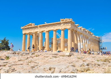 Athens, Greece - June 12, 2017: Tourists visit the Parthenon, a former temple dedicated to the goddess Athena and famous landmark in Athens, Greece