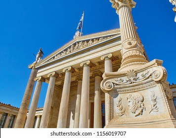 Athens, Greece - June 30, 2018. Principal facade of The Academy of Athens, Greece National academy, with Athena pillar in background and a lamp-post base decorated with a head of Zeus in foreground.