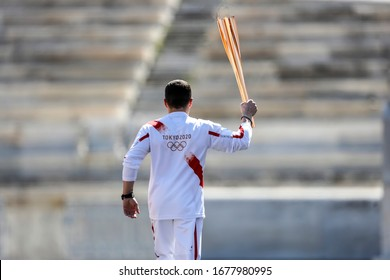 Athens, Greece - March 19, 2020: Olympic Flame handover ceremony for the Tokyo 2020 Summer Olympic Games. Greek Olympic medalist  E. Petrounias holds the Tokyo Olympic Flame at the Panathenaic stadium