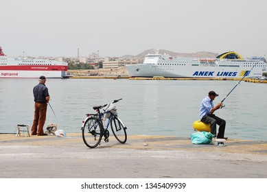 ATHENS, GREECE - MAY 11, 2016: Two male anglers fishing at Piraeus port. Piraeus is the largest passenger port in Europe and the second largest in the World.