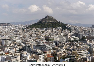 Athens, Greece Mount Lycabettus day view. Panoramic view of Lykavittos hill and surrounding cityscape buildings from Athens Acropolis.