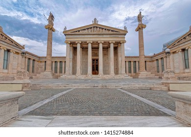 Athens Greece, the national academy classical building facade with Athena and Apollo statues standing on Ionian style columns under impressive sky