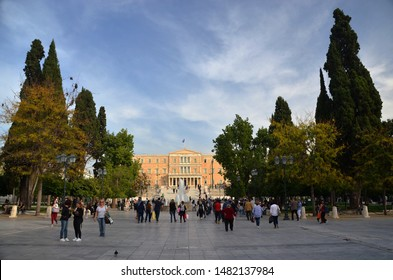 ATHENS, GREECE – NOVEMBER 1, 2018: Hellenic Parliament and neighbouring Syntagma Square with lots of people. Syntagma Square is a pulsing heart of Greek capital.