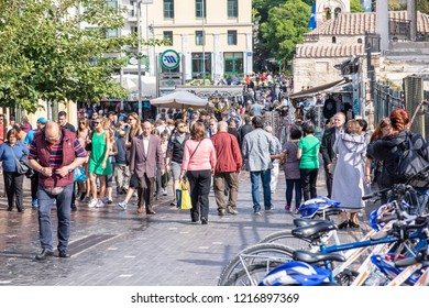 Athens, Greece - October 14, 2018: A crowd of people wander the famous Monastiraki Square, a popular public plaza in central Athens, near the Acropolis. Millions visit Athens yearly.