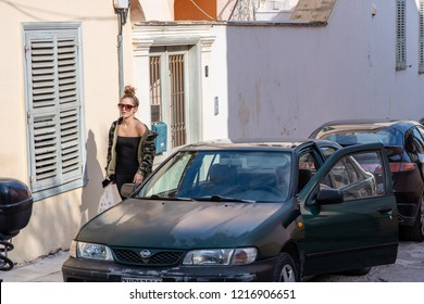 Athens, Greece - October 14, 2018: Street scene in the Plaka neighborhood - a stylish woman walks home after running errands, past a man parking his car.