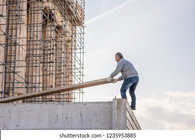 Athens, Greece - October 16, 2018: A construction worker carries equipment, working on the restoration of the ancient Parthenon Temple in the Acropolis. The Acropolis is currently being restored.