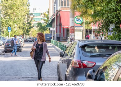 Athens, Greece - October 18, 2018: A stylish young woman runs errands in the trendy Gazi neighborhood, known for its nightlife and art culture.