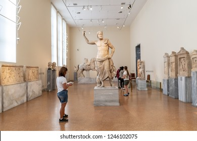 Athens, Greece - October 19, 2018: A woman views the famous sculpture, Poseidon of Melos, dated to the second century B.C., at the National Archaeological Museum.