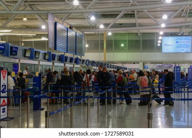 Athens, Greece - October 28 2017: airport check-in gates & departurtes board. Passengers waiting in line at service counters prior to departure in Athens International Airport Eleftherios Venizelos.