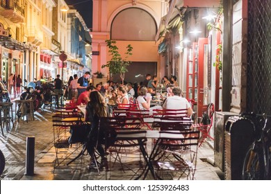 ATHENS, GREECE - SEPTEMBER 16, 2018: Night views of Athens city. People relaxing after work. Outdoor restaurant at Plaka by night in Athen, Greece