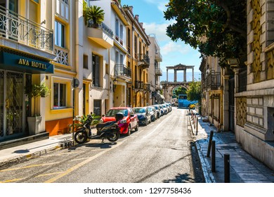 Athens, Greece - September 16 2018: View from a quiet street as traffic passes by The Arch of Hadrian, most commonly known in Greek as Hadrian's Gate in the historic center of Athens, Greece.
