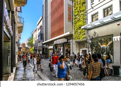 Athens, Greece - September 17 2018: Local Greeks and tourists walk near the Church of Panagia Kapnikarea, the oldest church in Athens, in the busy shopping district of Ermou Street.