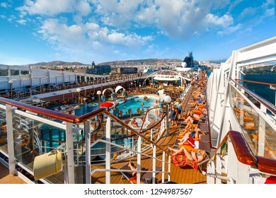 Athens, Greece - September 18 2018: Tourists lounge in the sun, swim and party on the upper deck of a large cruise ship as it leaves the port of Athens, Greece.