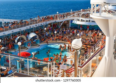 Athens, Greece - September 18 2018: Tourists lounge in the sun, swim and party on the upper deck of a large cruise ship