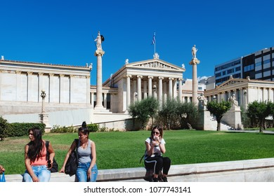 Athens, Greece - September 22, 2017: Street view of the Academy of Athens is the national institution for sciences, humanities and arts. Young girl and student sitting on parapet in foreground.
