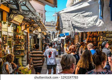 Athens, Greece - September 22 2018: Tourists walk the narrow path between souvenir shops and outdoor vendors selling gifts in the touristic Plaka section of Athens, Greece.