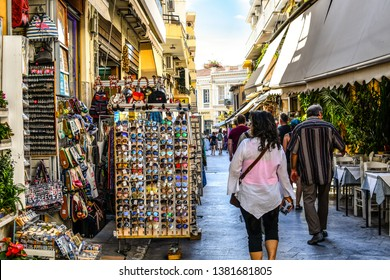 Athens, Greece - September 22 2018: Tourists walk the streets lined with souvenir shops and outdoor sidewalk cafes in the touristic Plaka section of Athens, Greece.