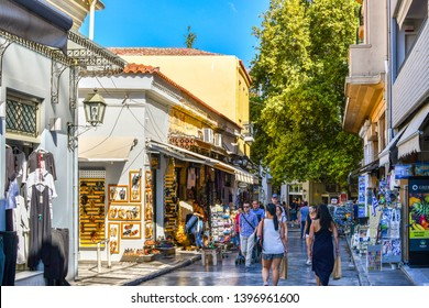 Athens, Greece - September 22 2018: Tourists pass gift and souvenir shops in the touristic Plaka section of Athens, Greece.