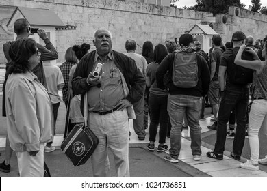Athens - Greece. September 30, 2017. A couple of tourists is not intrigued by the ceremony performed by the presidential guard at Syntagma square.