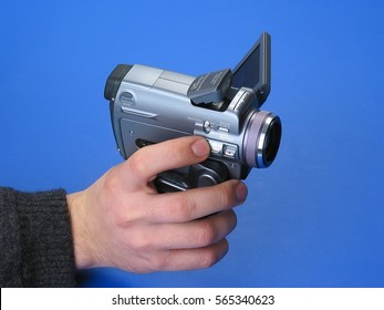 ATHENS, GREECE-JANUARY 28, 2003: Caucasian male hand holding an amateur mini DV video camera on blue background