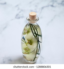 Athens January 19th .Bottle filled with SPA oil and moth orchid flower petals inside it. Isolated on white marble background. Athens: 19th January 2019, Greece.  Stock Image