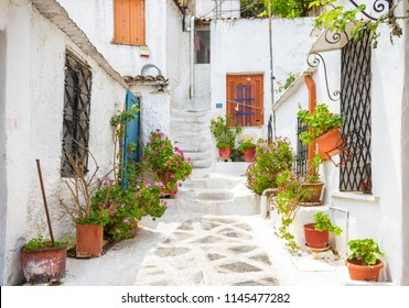 Athens - May 6, 2018: Scenic narrow street in Anafiotika, Plaka district, Athens, Greece. Plaka is one of the main tourist attractions of Athens. Nice traditional alley at Acropolis slope in Athens.