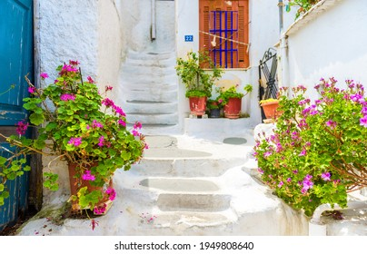 Athens - May 6, 2018: Street in Plaka district, Athens, Greece. Plaka is tourist attraction of Athens. Beautiful sidewalk stairway near Acropolis in Anafiotika quarter. Cozy stairs between old houses