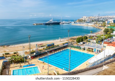 Athens - May 7, 2018: Sea beach in Piraeus, Greece. Scenic view of beautiful waterfront. Panorama of the city seaside with swimming pools and docked yachts. Luxury marine relax on the coast of Athens.