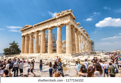 Athens - May 8, 2018: People visit the Parthenon on the Acropolis in summer, Athens, Greece. It is a main tourist attraction of Athens. Ancient Greek ruins on a top of Acropolis hill in Athens center.