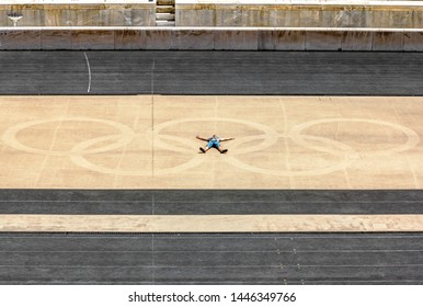 Athens.Greece.May 31, 2019. The man lies with his arms outstretched against the Olympic rings on the field Panathenaic stadium in Athens.
