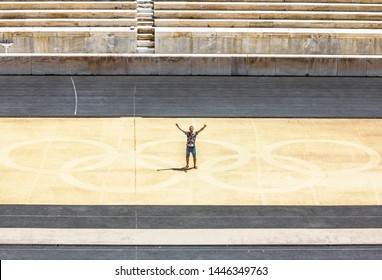 Athens.Greece.May 31, 2019. A man stands with his arms outstretched against the Olympic rings on the field of Panathenaic stadium in Athens.