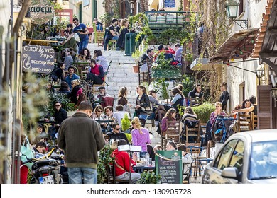 ATHENS,GREECE - MAR 09 : The touristic season is opening and tourists start visiting the famous Plaka area under Acropolis, March 09, 2013 in Athens,Greece