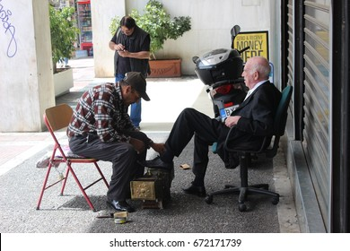 ATHENS,GREECE, MARCH 2016. A greek gentleman having shoeshine on a beautiful day during midday in Athens.