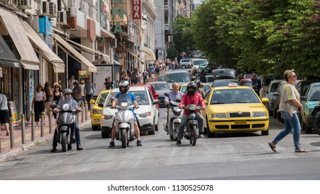 Athens,Greece - May 1,2018 -Street scene in the city center of the Greek capital with cars, yellow cabs, busy traffic, people, residents, shops, buildings and blue sky in background.