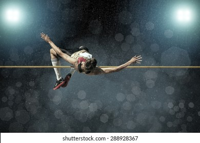 Athlete in action of high jump under rain and bokeh background.