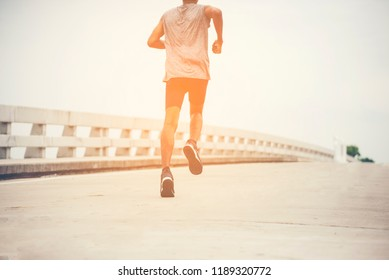 Athlete active man running outside road with sprint speed.Runner exercise sport traning to triathlon marathon run with endurance workout in the sunrise.Healthy jogger lifestyle on fitness  street