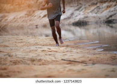 Athlete active man running outside road with sprint speed.Runner exercise sport traning to triathlon marathon run with endurance workout in the sunset.Healthy jogger lifestyle beside river.