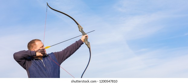 Athlete aiming at a target and shoots an arrow, toned