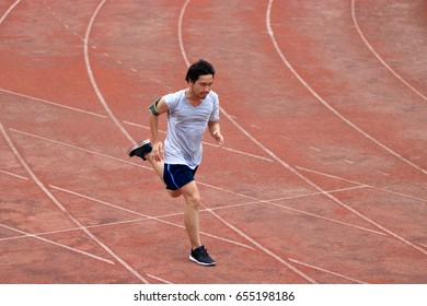 Athlete Asian man running on racetrack in stadium. Healthy active lifestyle concept.