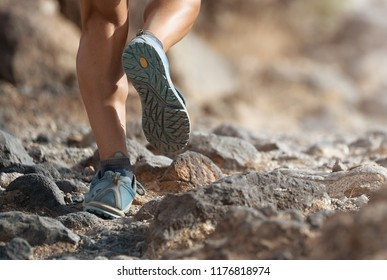Athlete with athletic sneakers jogging or running nature. Athlete runs on mountain rocky path. Healthy lifestyle concept