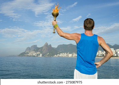Athlete in in athletic uniform standing with sport torch above Rio de Janeiro Brazil skyline at Ipanema Beach