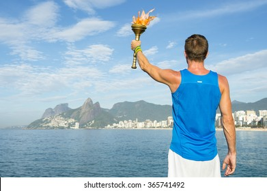 Athlete in athletic uniform standing with sport torch in front of Rio de Janeiro Brazil skyline at Ipanema Beach