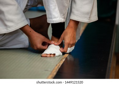 The athlete bandages his injured leg before judo training. Judo barefoot on tatami