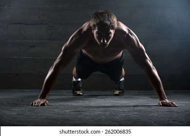 Athlete with a beautiful body and a naked torso doing push-ups exercise on the floor. Studio shot in a dark tone.