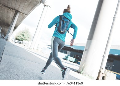 Athlete beautiful girl with water-backpack runnig in the morning on the city street. Sport tight clothes. Urban workout.