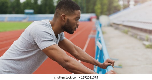 Athlete black man getting ready for workout on stadium. Preparing for trainig concept