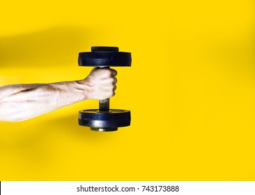 athlete bodybuilder, holding in hand a dumbbell, muscular hand on a yellow background, your text there, flat, concept sports lifestyle