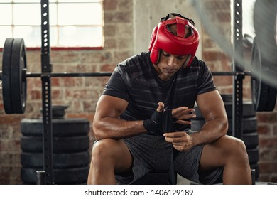 Athlete boxer in sportswear tying bandage on hand and wearing red boxing helmet. Mature boxer with head gear wearing hand gloves. African man preparing for boxing practice at gym.